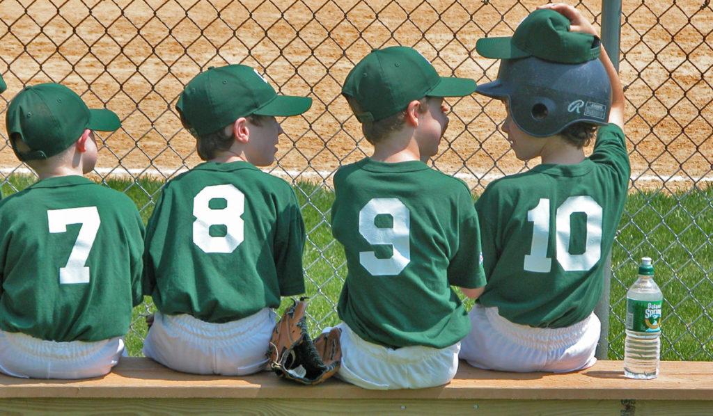 little league baseball players on a bench